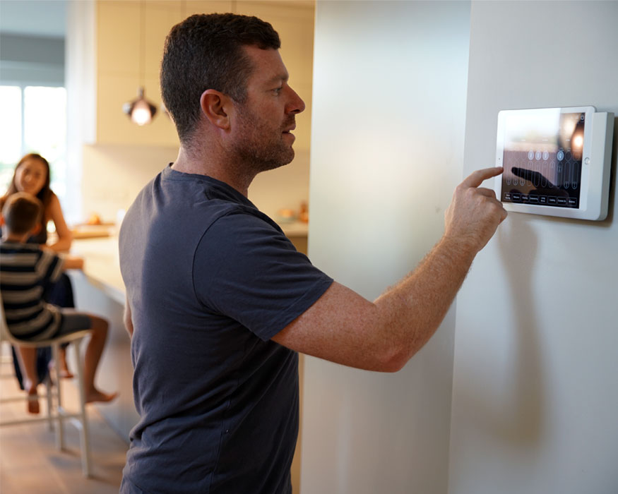 Man using table device on wall to control Clipsal products