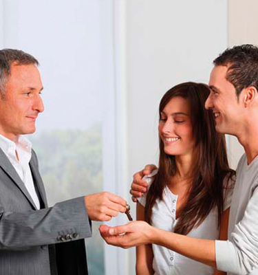 Man handing keys to new home owners