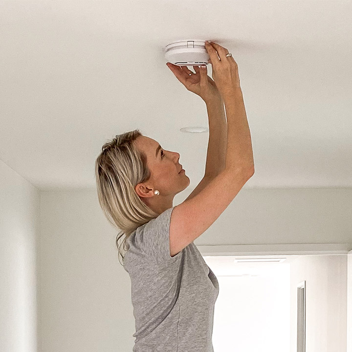 Woman changing battery in chirping smoke detector