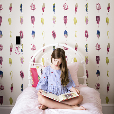 Young girl reading in her room while her phone charges on an Iconic USB charger shelf.
