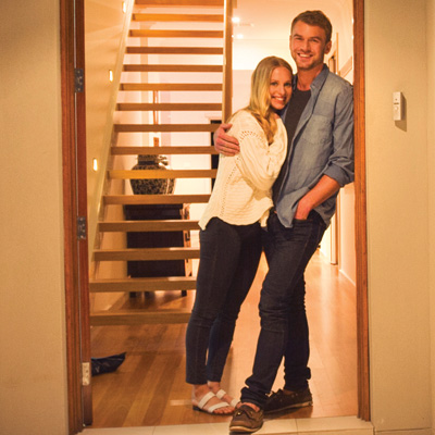Young home owner couple in the doorway of their new home.