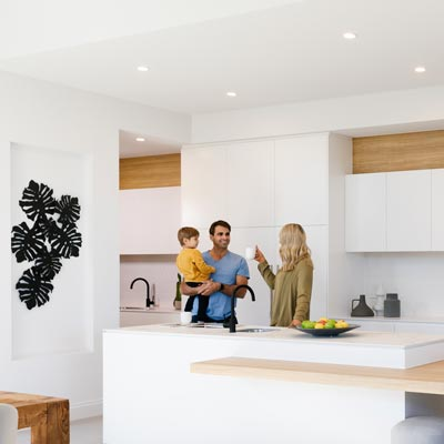 A family in their kitchen enjoying Clipsal's stylish lighting