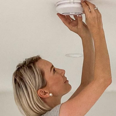 Smart home owner routinely checking her Clipsal Smoke Alarm